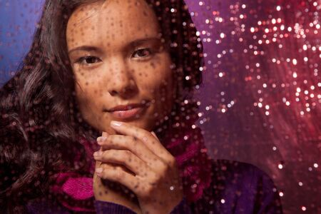 Beautiful Asian woman behind the glass in rainy weather  with street light reflecting photo