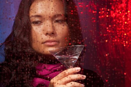 Sad Asian woman with drink in cold rainy weather behind the glass photo