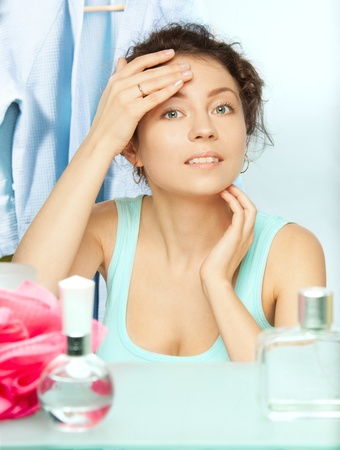 Woman inspecting skin for spots in the morning looking at the mirror photo