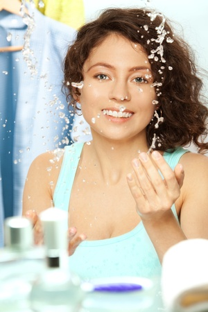 Charming smiling young woman washing her face photo