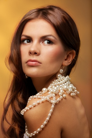 Portrait of young woman with pearls necklace on golden background