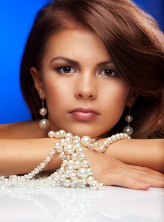 Portrait of young woman with  pearls necklace on blue photo