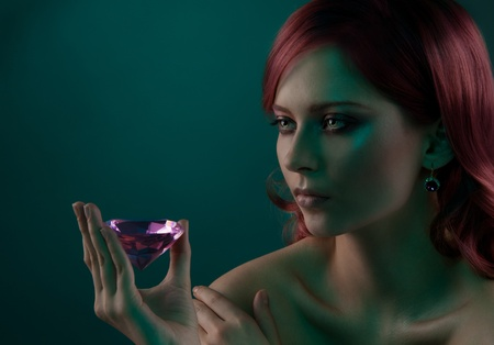 Beauty portrait of woman with big pink diamond photo