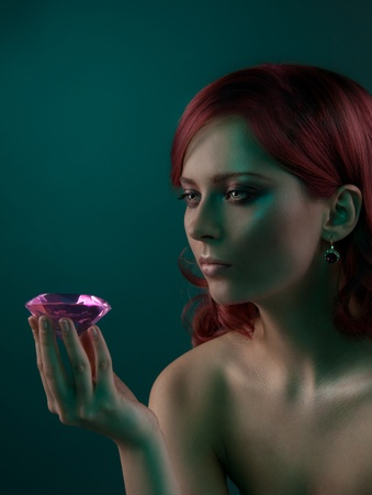 Beauty portrait of woman with big pink diamond on dark background photo