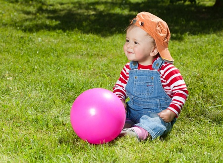 Happy, smart toddler sit with pink ball in the garden