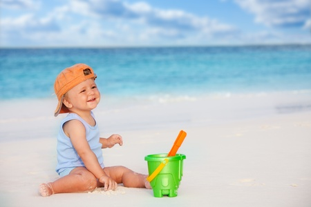 Happy laughing kid playing with scoop sitting near the ocean Stock Photo - 11753336