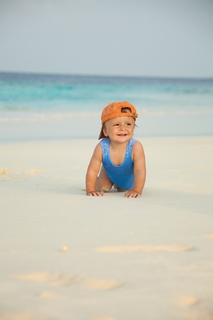 Happy kid crawling on the beach with white sand and sea on the background photo