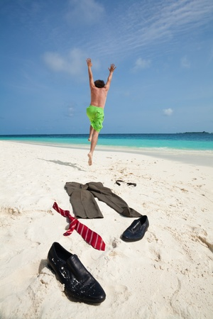 Happy business man running in to ocean to swim with clothes such as boots, tie and pants taken off and laying on the white sand photo