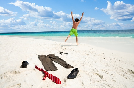 Happy business man running and jumping to the sea throwing away formal clothes photo