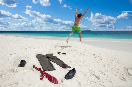 Happy business man running in to ocean to swim with clothes such as boots, tie and pants taken off and left on the white sand photo