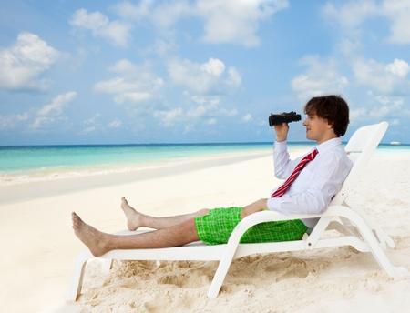 Hombre de negocios sentado en la tumbona y mirando a través de los prismáticos, que llevaba la camisa formal y corbata roja