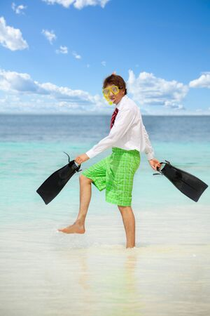 Businessman wearing snoring mask with flippers and wearing formal clothes with red tie entering water on the beach photo