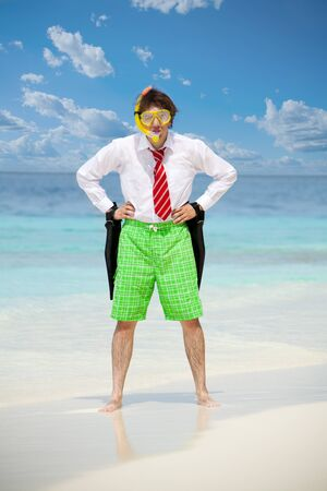 Business man wearing white shirt  and tie and also scuba, mask and holding flippers on the beach in angry pose photo