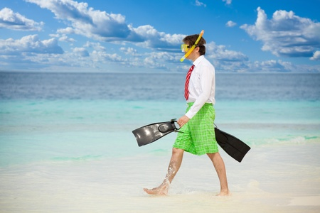 formal clothes: Businessman entering the ocean waters wearing snoring mask with flippers and wearing formal clothes with red tie entering water on the beach Stock Photo