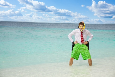 Angry businessman standing in the water on the beach with flippers photo