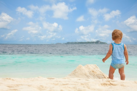 Toddler playing with sand on the tropical white beach Stock Photo - 11753322