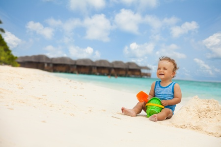 Toddler laughing sitting with toys and playing with sand photo