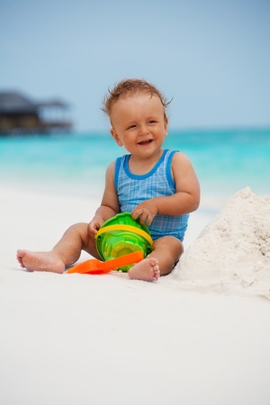 Kid playing with sand sitting on the Maldivian beach photo
