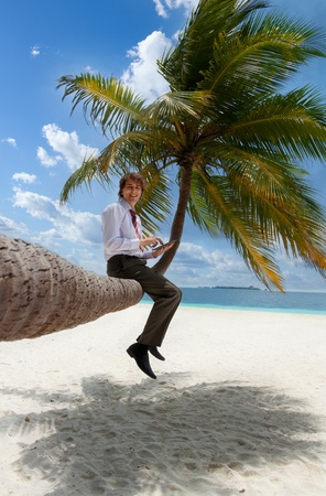 palm computer: Businessman with tablet pc sitting on palm tree on the Maldivian beach and looking at camera smiling Stock Photo