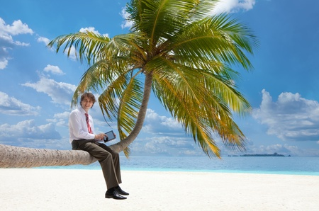 Office manager with tablet pc sitting on palm tree on the Maldivian beach and looking at camera smiling photo