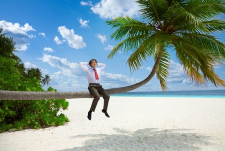 Happy businessman in formal clothes and tie sitting on the palm and relax photo