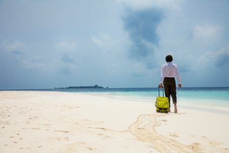 business man with suitcase walking on the beach