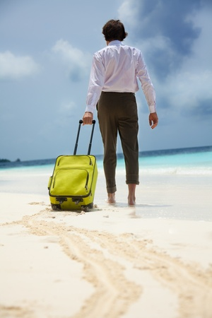 White-collar worker on the beach vacation - walking with green suitcase Stock Photo - 11753332