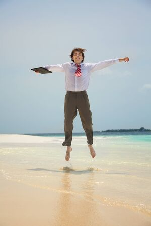 Happy young white-collar worker jumping on the shore of the sea photo