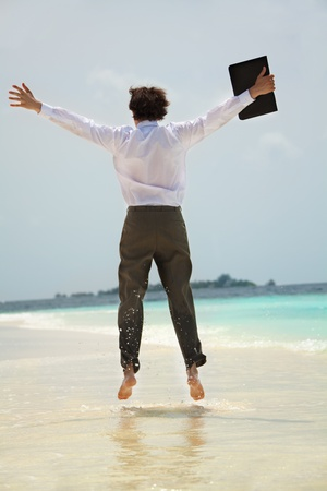 Happy young white-collar worker jumping on the shore of the sea view from behind photo