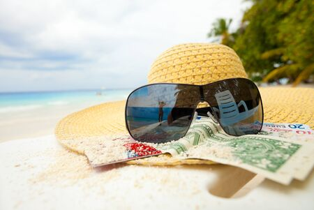 Straw hat, money, bank card, shades with relaxing woman mirrored in it Standard-Bild