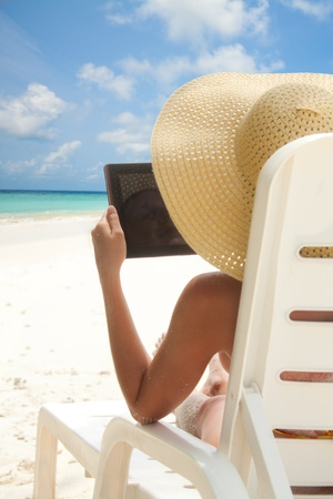 Woman sitting on the beach and browsing internet with tablet computer sitting in the deck chair photo