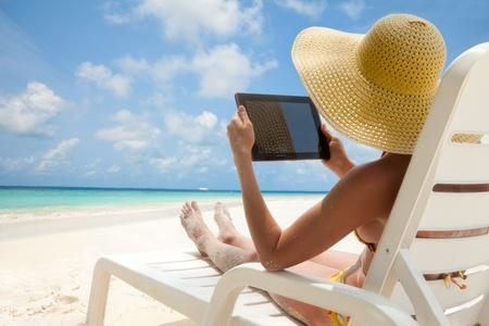 """Kobieta trzyma komputer tablet siedzi na plaży w leżaku i kÄ…pieli sÅ'oÅ""""ce Zdjęcie Seryjne"""