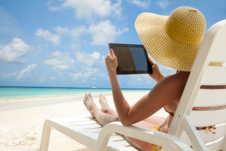 Woman holding tablet computer sitting on the beach in deck chair and taking sun bath photo