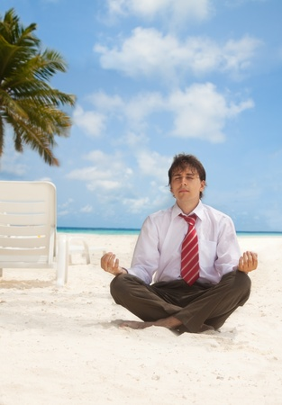 Office worker sitting on the beach an meditating photo