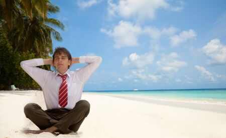 Businessman sitting on the beach and relaxing