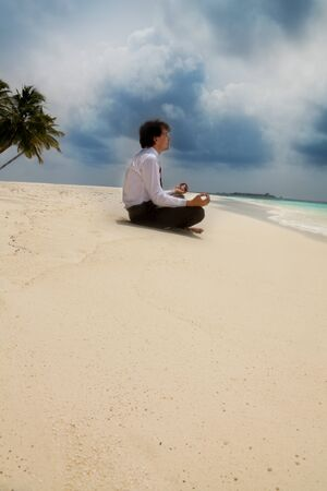 Calm business man sitting on the beach in lotus pose and meditation photo