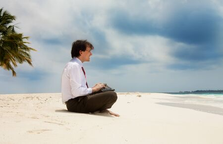 Happy young office worker sitting on the sand near the sea with keyboard photo