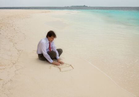 Businessman typing on keyboard of laptop drawn on the sand photo