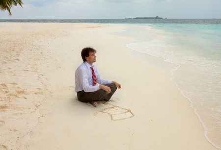 Calm happy  office manger sitting on the sand with computer drawn on the sand photo