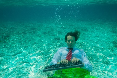 swimming suit: Office worker wearing formal clothes with keyboard underwater Stock Photo