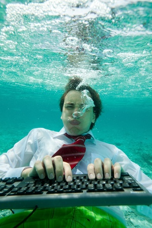 Yong man in formal clothes working with keyboard underwater with intense face expression photo