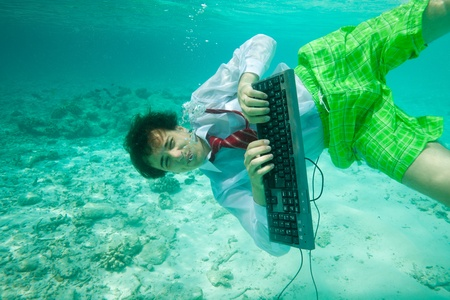 Young man wearing shirt and red tie with keyboard swimming and typing underwater photo