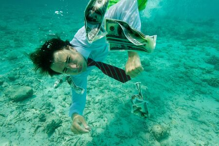 money laundering: Business man collecting money swimming underwater, wearing formal clothes Stock Photo