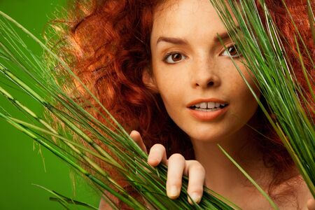 red hair beauty: Beauty portrait of woman looking through bush Stock Photo