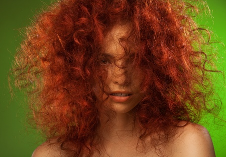 Red curly hair woman beauty portrait with her face partly hidden on the green background