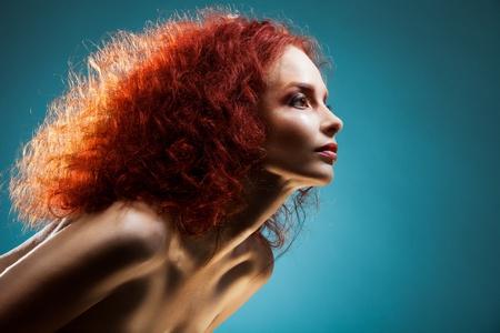 파란색 배경에 곱슬 빨간 머리를 가진 대시와 자신감 여자의 아름다움 초상화