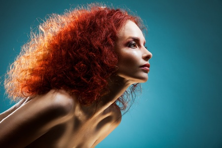 Beauty portrait of dashing and confident woman with curly red hair on blue background