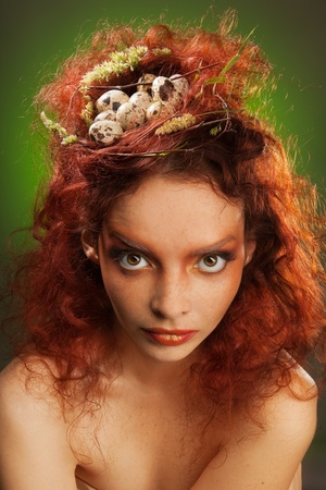 Beauty portrait of a woman with birds nest in curly red hairs photo