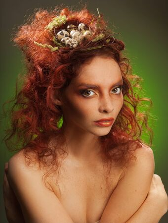 Beauty portrait of a red curly hair woman with birds nest with eggs in her hairstyle Stock Photo - 11753897
