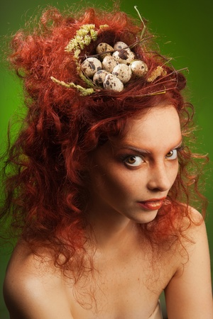 Beauty portrait of woman with nest in curly red hair photo